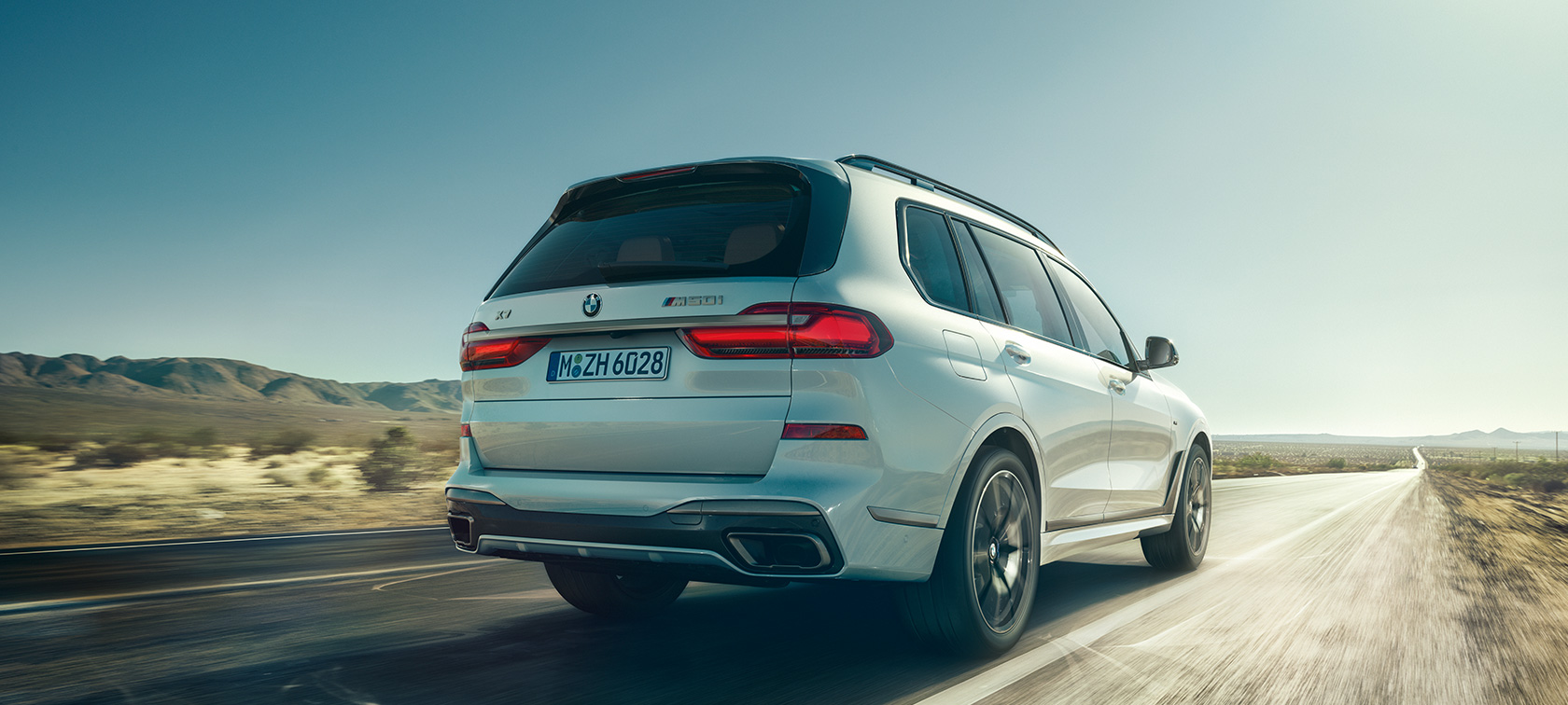BMW X7 M50d in Mineral White, driving on an empty highway, rear view, G07, 2019